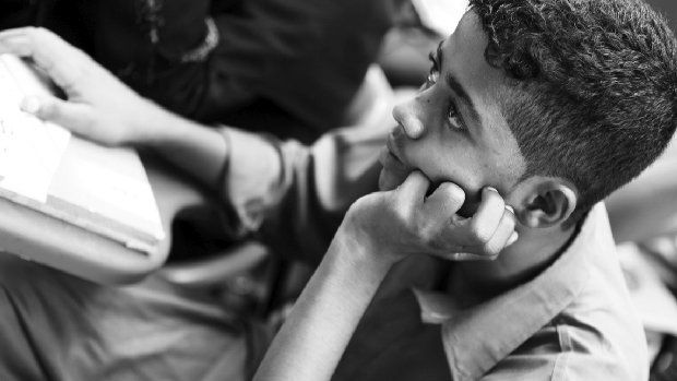 Photo of a student with a hand under his chin