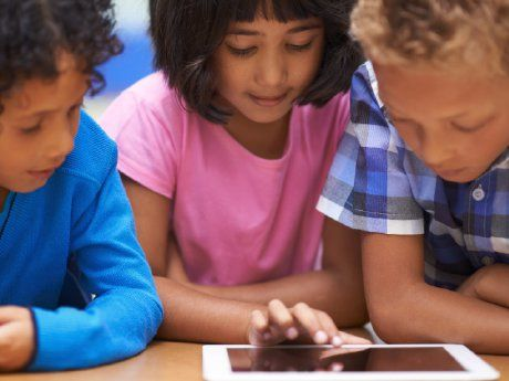 Three children around a tablet device