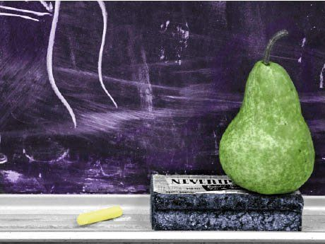 A photo of a pear on an eraser, on a chalkboard shelf.
