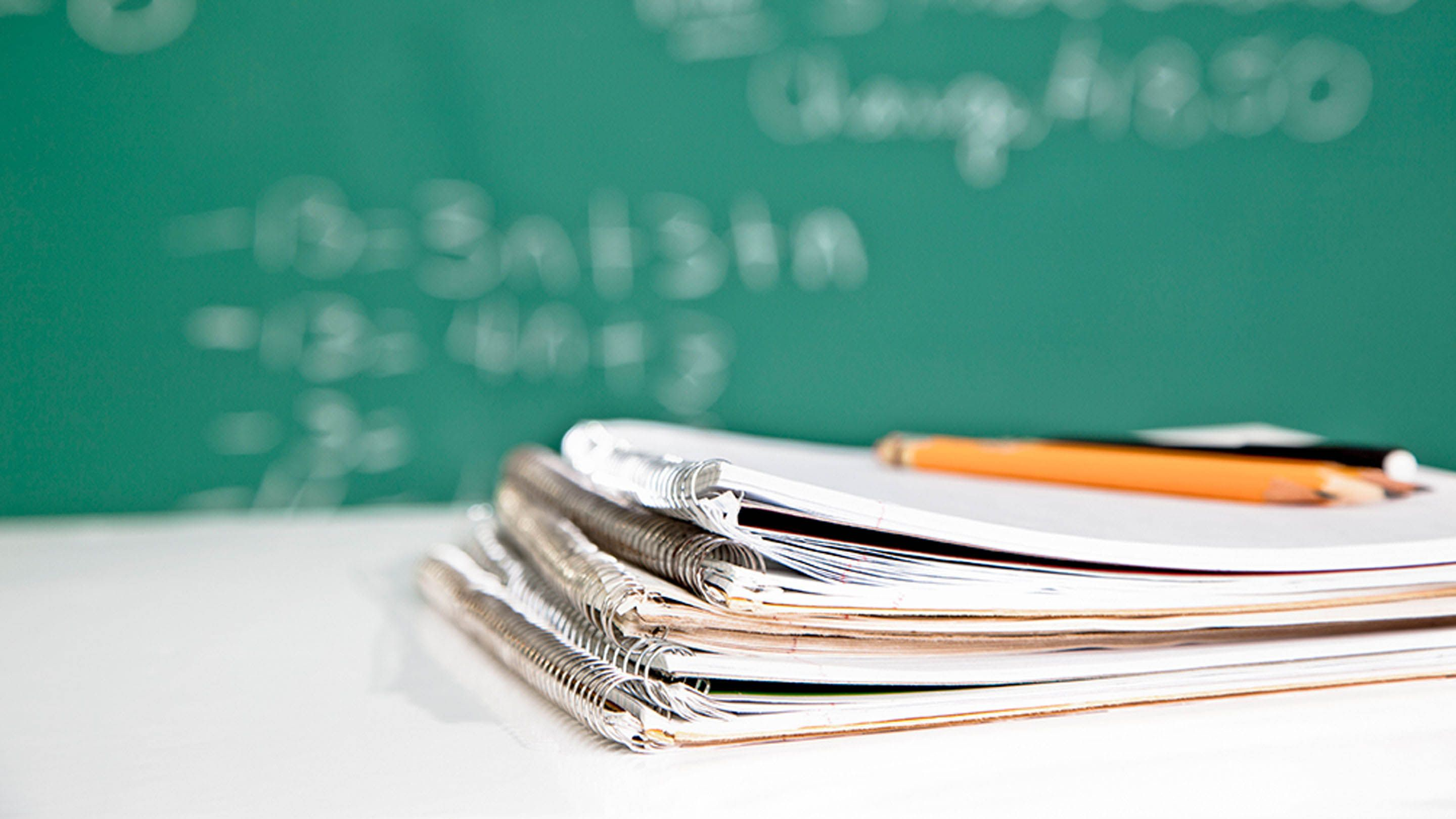 A stack of four notebooks are on a classroom desk with three pencils lying on top of them. A blurred out chalkboard is shown in the background.