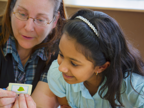 A photo of a female teacher working with an elementary-school girl.