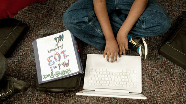 Student sitting on the floor working on his laptop
