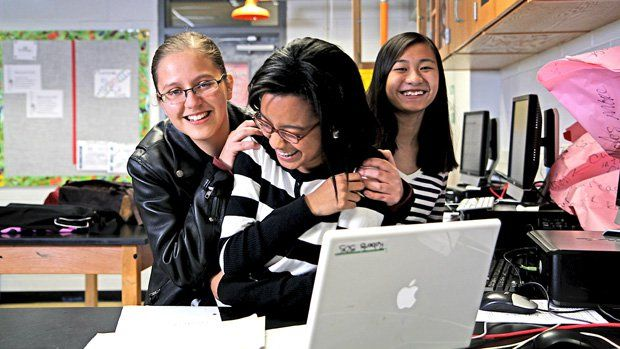 Three girls smiling behind a laptop
