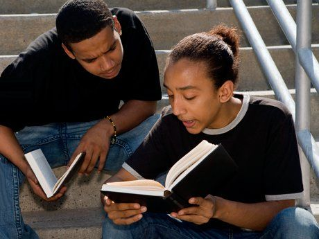 Two young men with open books in discussion