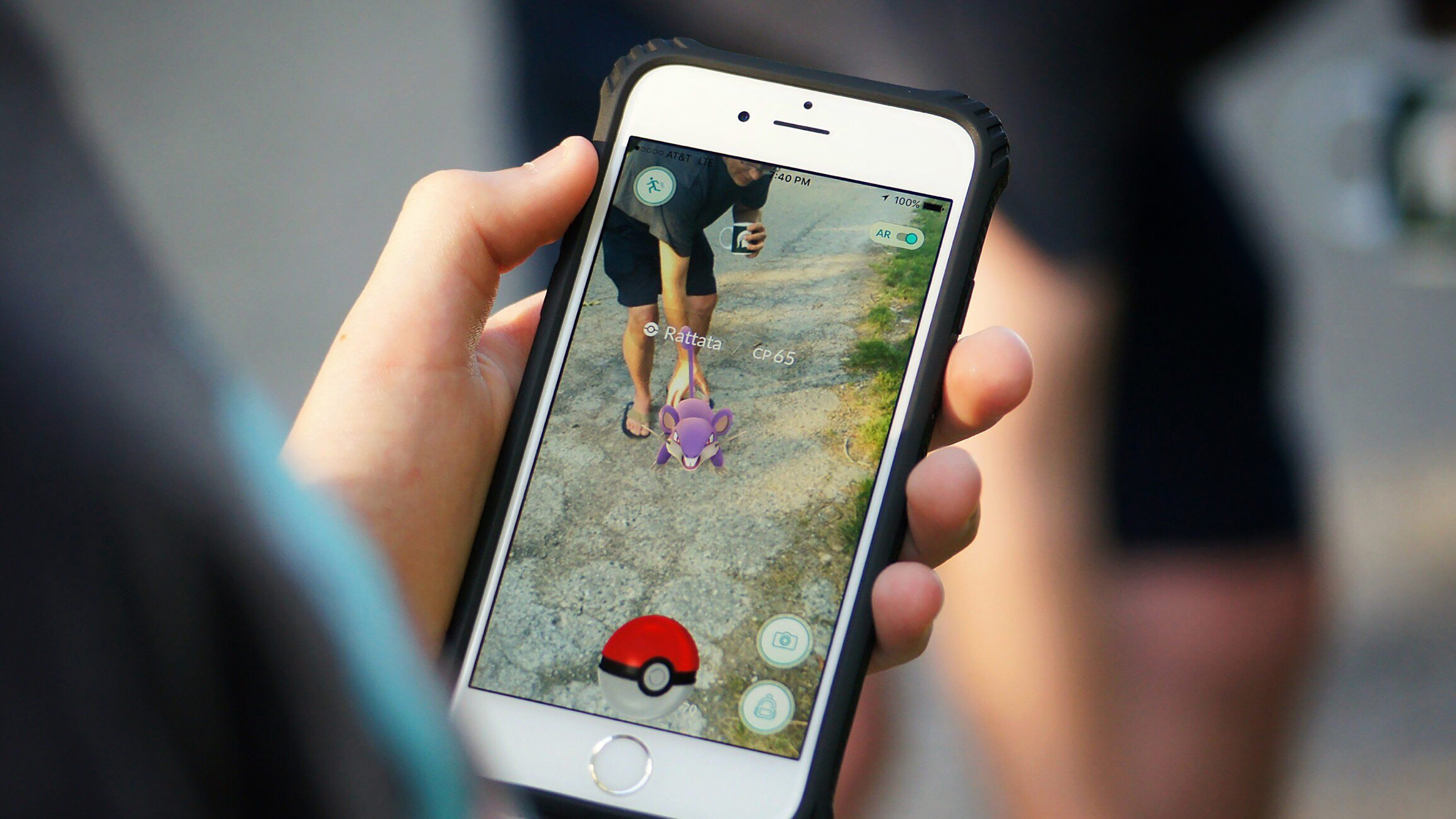 A person is holding a smartphone with Pokemon Go showing on their screen. They're taking a picture of someone bent over, holding a coffee cup, and touching a purple rat Pokemon.