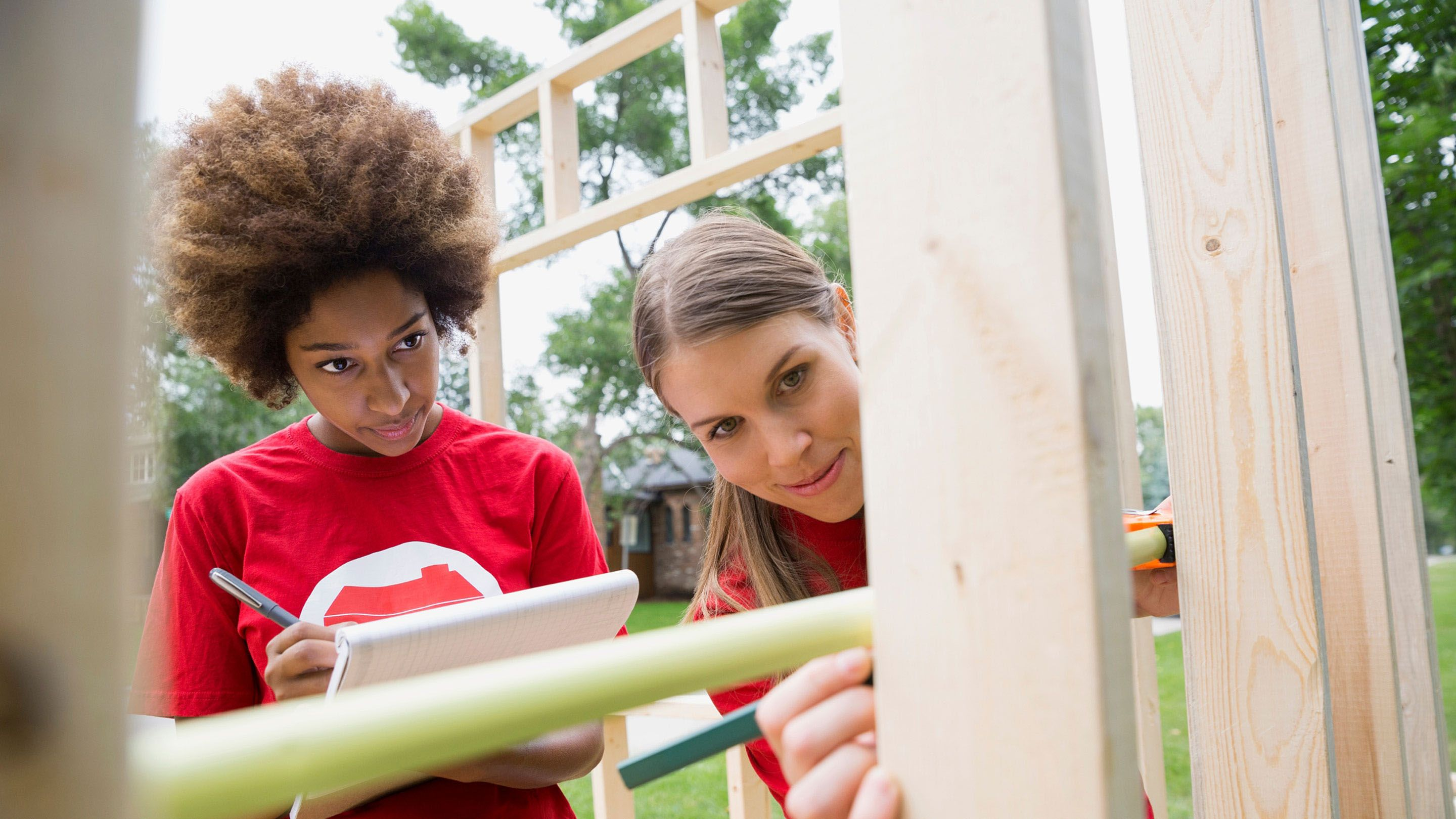 Two young women work on a building under construction.