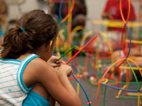 A photo of an elementary-school girl creating a model with colorful sticks.