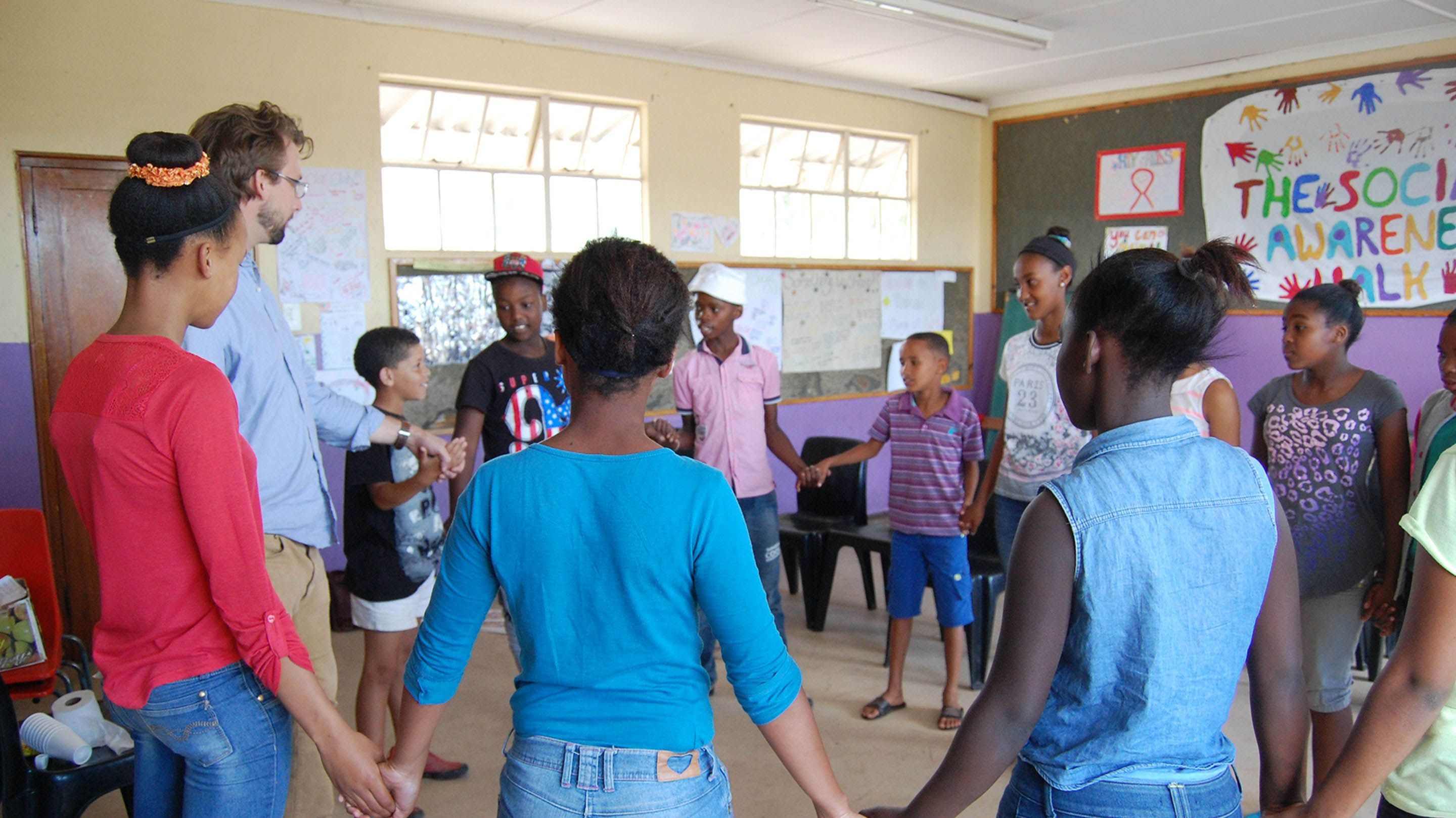 A teacher and a group of students stand in a circle holding hands.