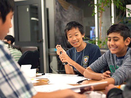 Three boys working together around a table