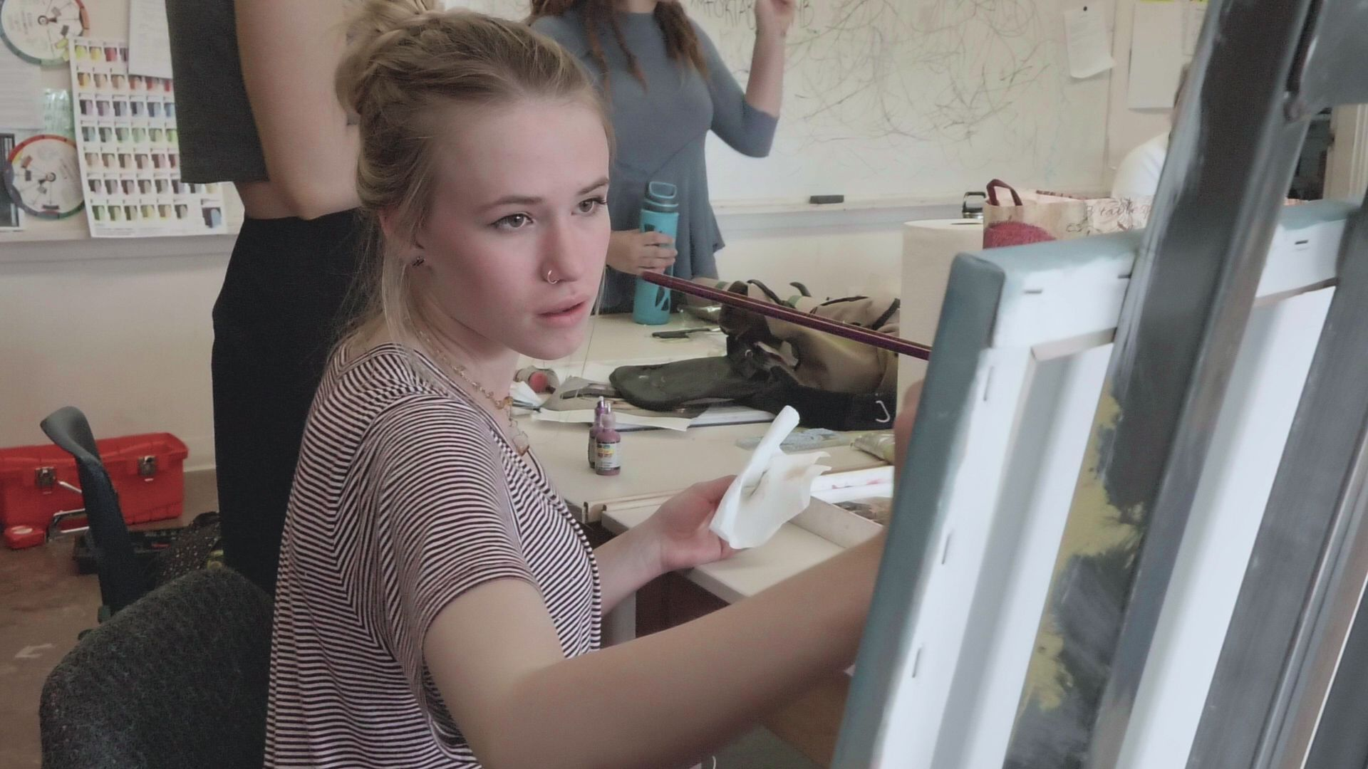 A female teen is sitting in an art class, holding a long paint brush, painting on a canvas.