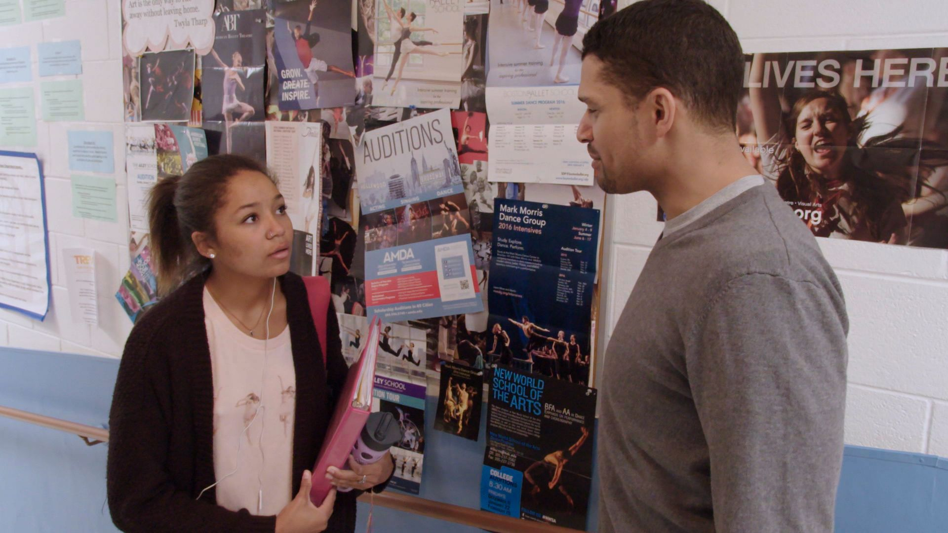 A female teen is standing in a school hallway talking to a male teacher; there are dance fliers on a bulletin board on the wall beside them.