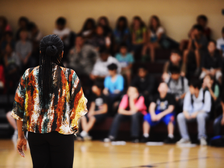 A photo of a woman talking to a large group of students in a school auditorium.