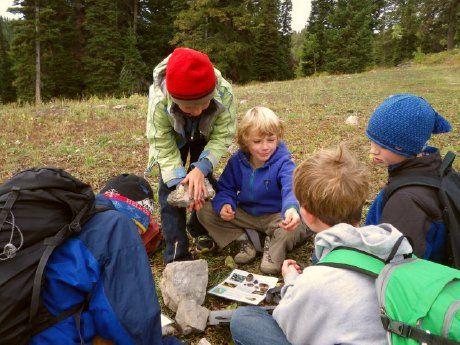 Five children bundled up in a forest identifying rocks