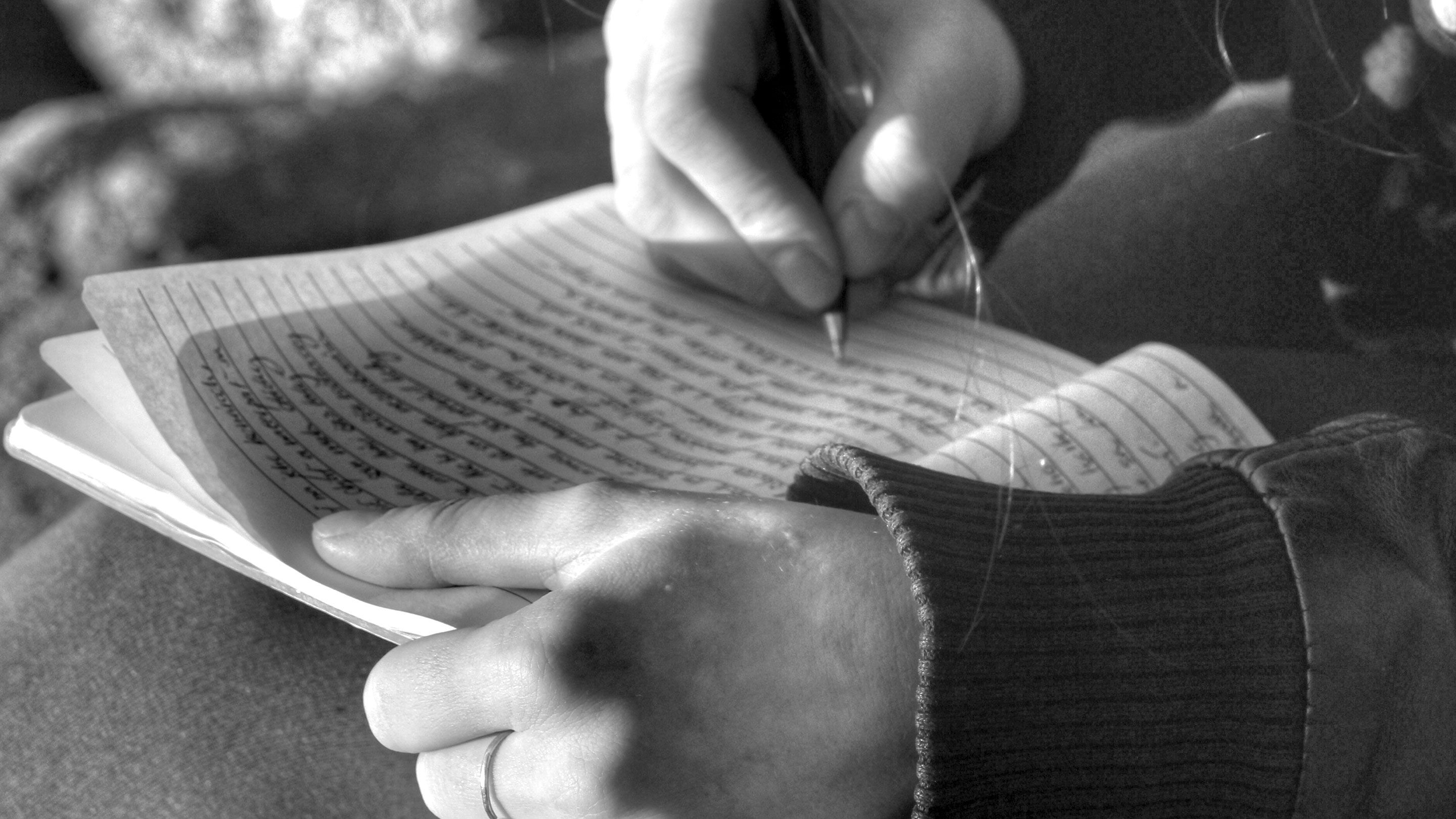 Close-up black-and-white photo of a student's hands as they write in a journal.