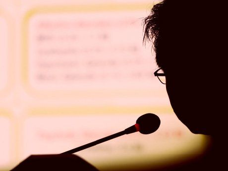 Silhouette of a person speaking while looking at data projected on a screen