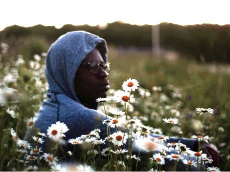 Older boy with grey sweatshirt hood on sitting in a field of daisies