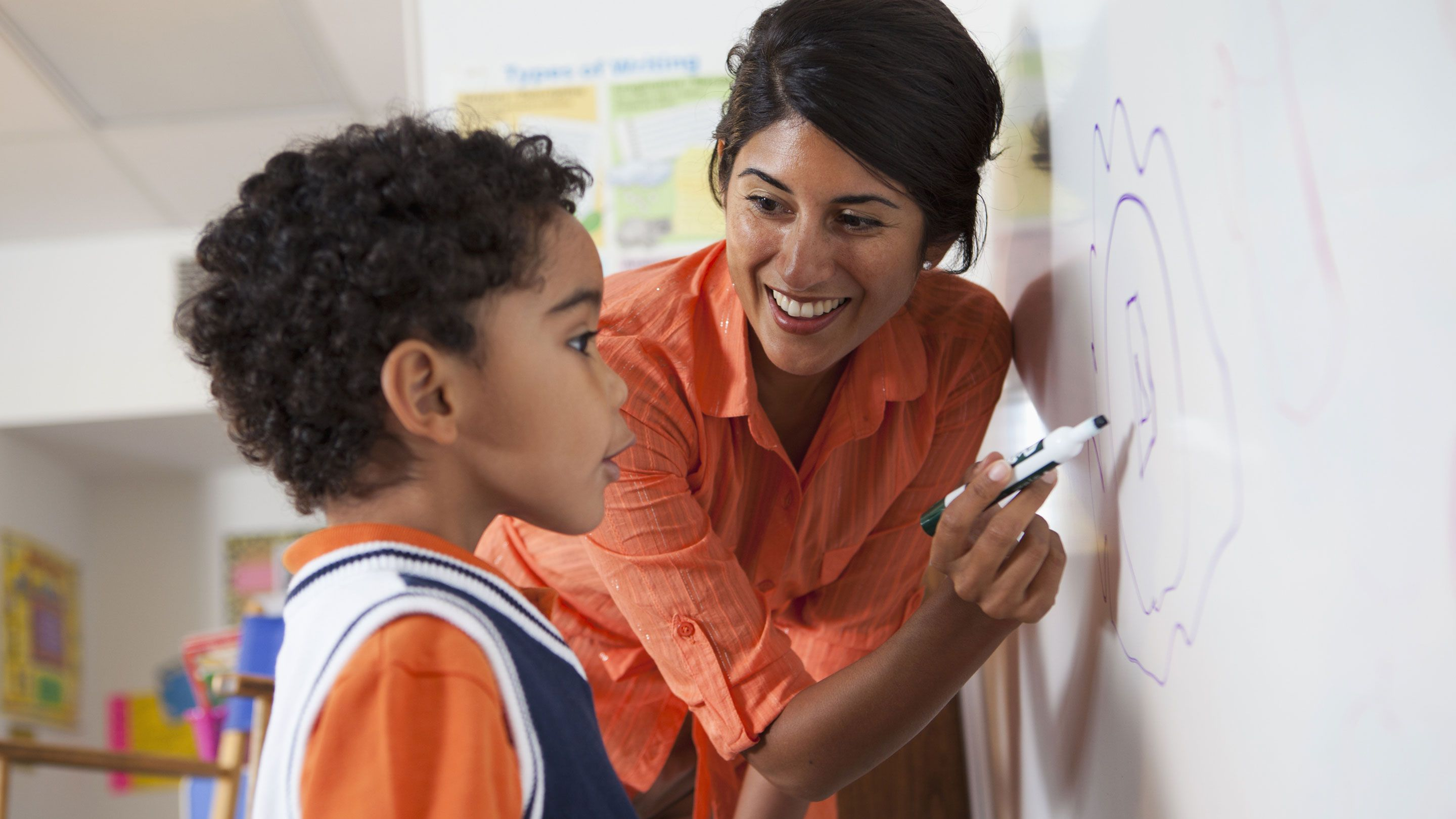 A teacher works at the white board with a young boy.