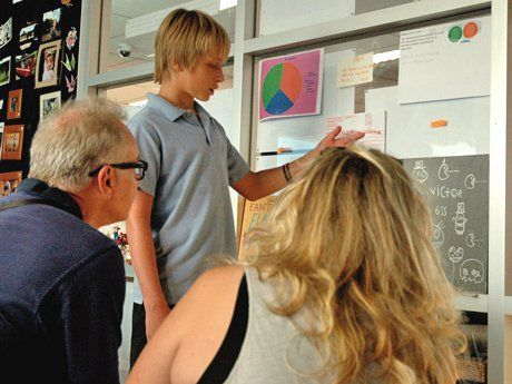 A young boy is standing in front of a board in a classroom, pointing to something and talking to two adults.
