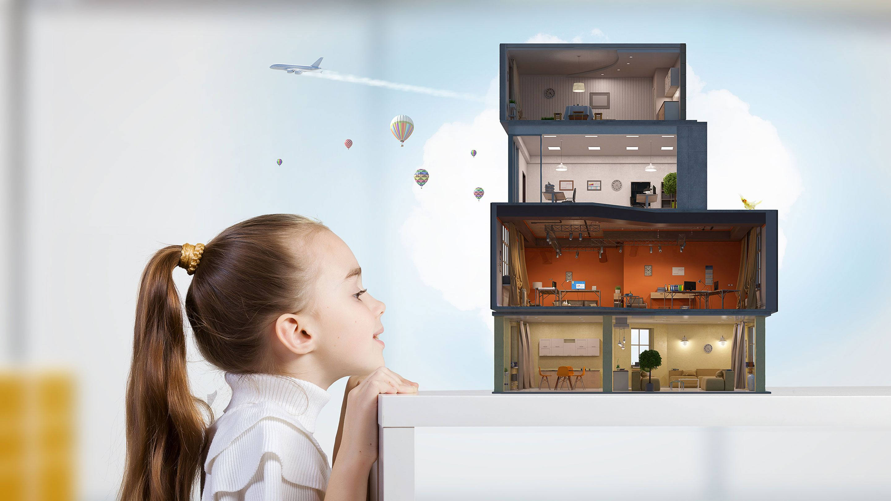 A young girl imagines that a pile of small boxes on a table are a house complete with electricity, with a plane and hot-air balloons flying above.