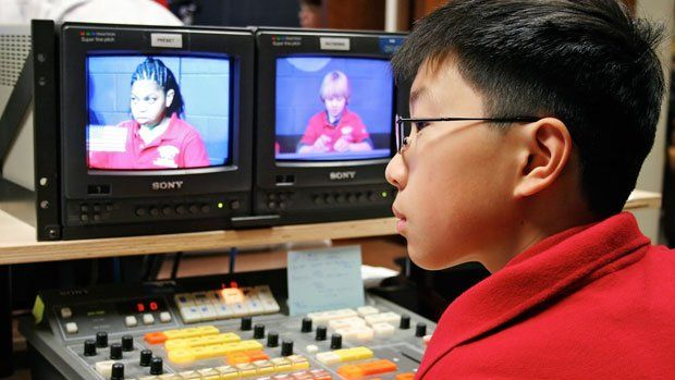 Boy at monitors and mixing board for school broadcast