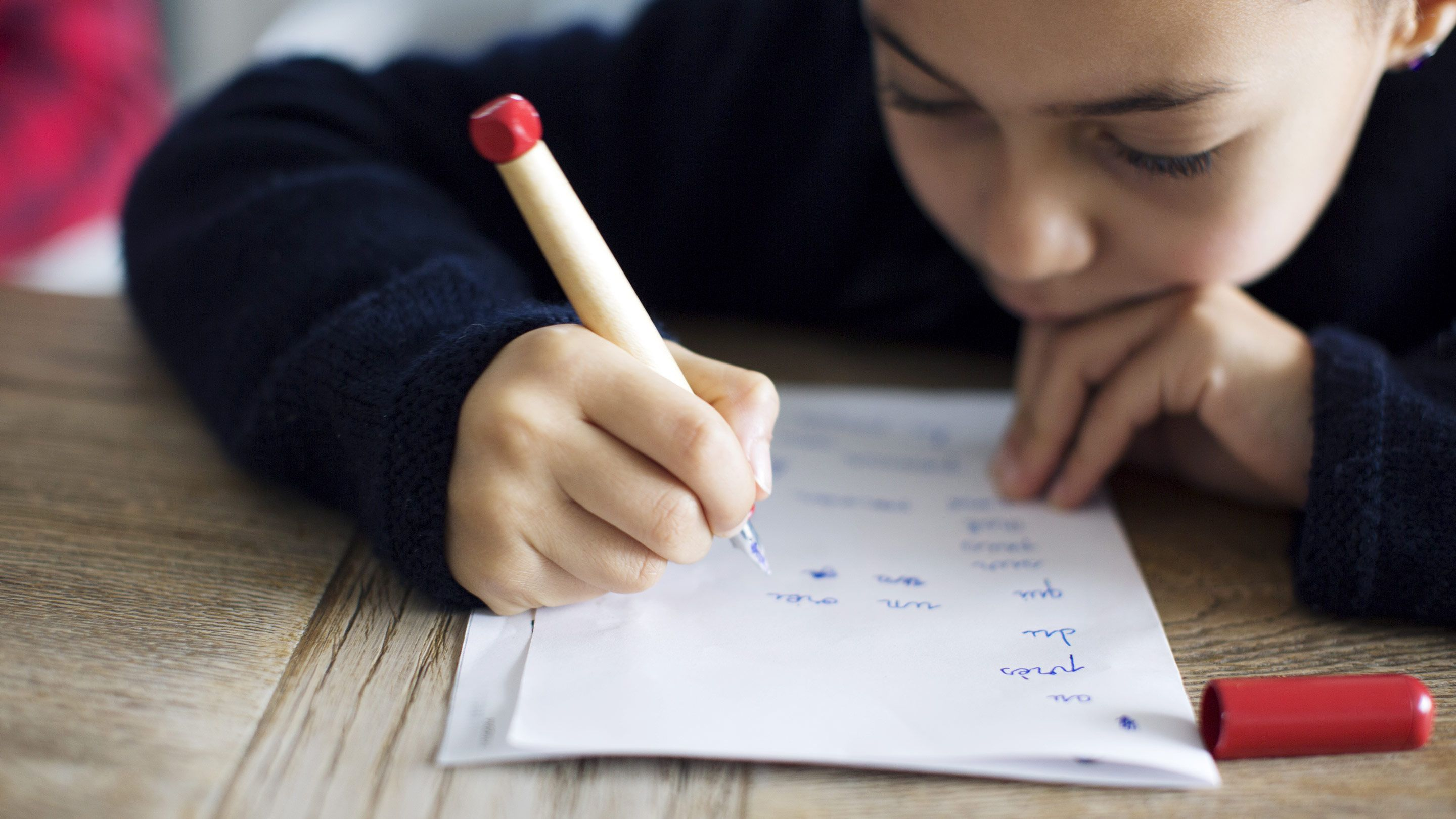A young student does classwork in pen.