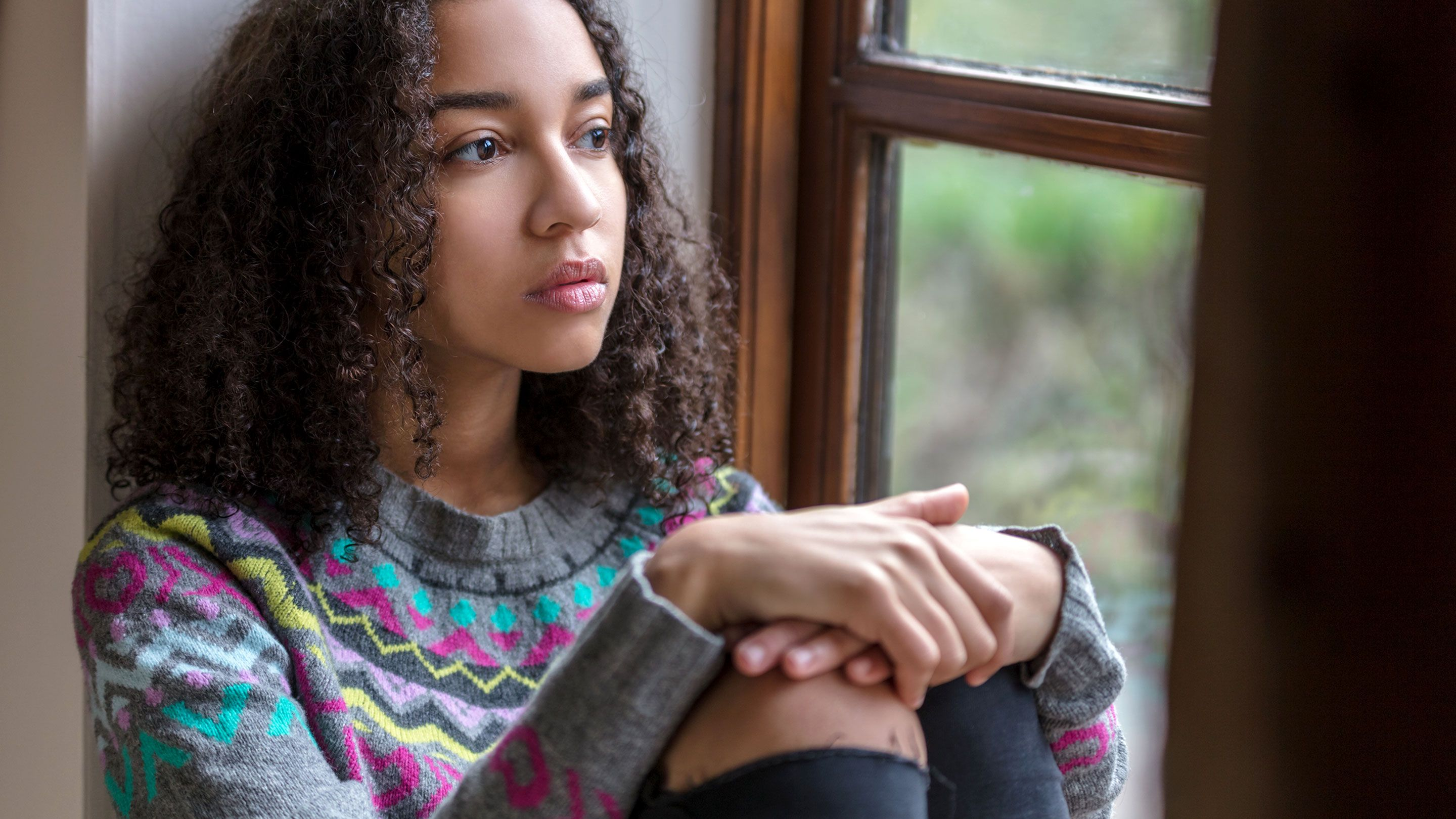 A black female high school student looks out a window