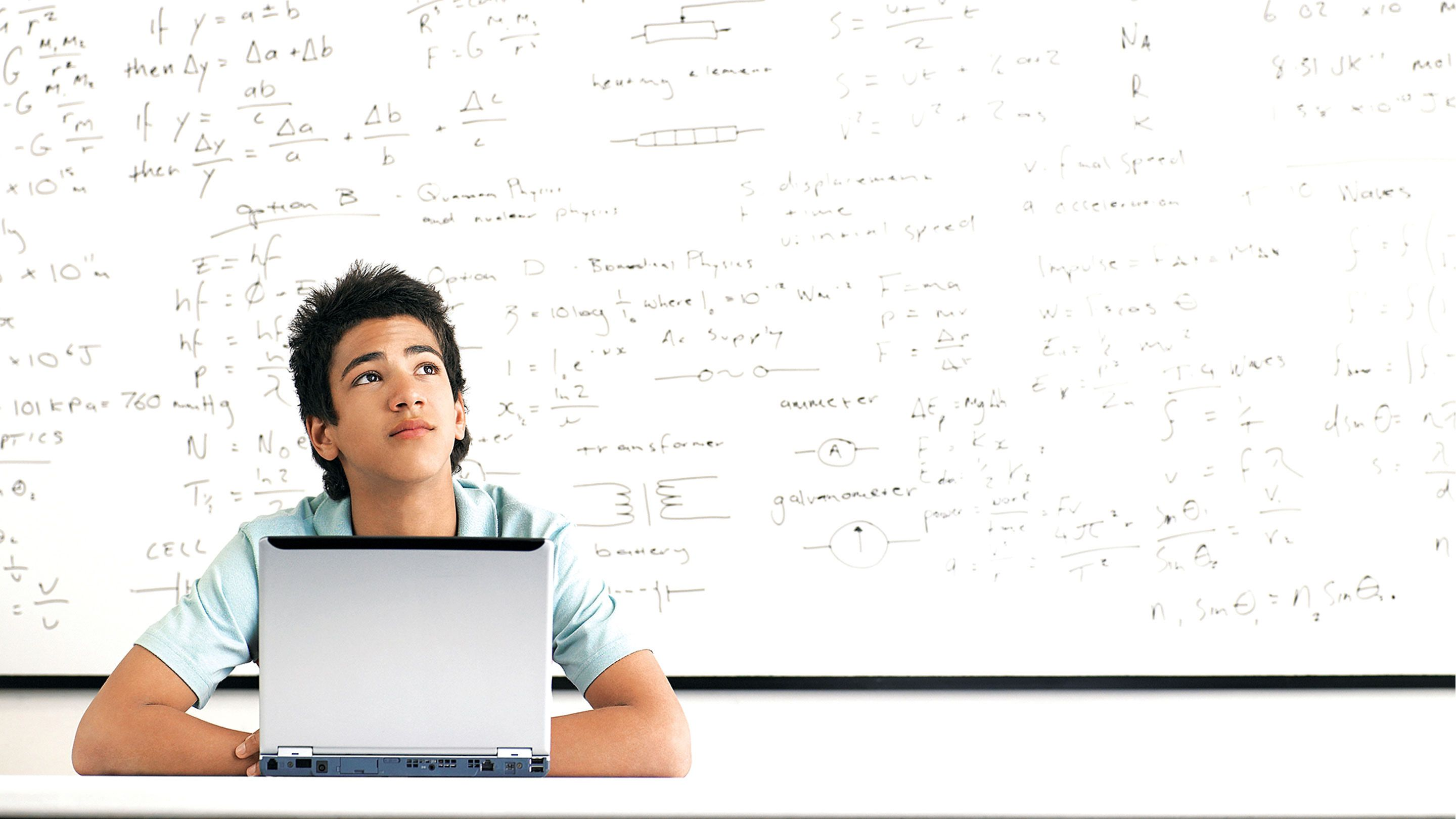 A student works at a desk in front of a whiteboard covered with equations.