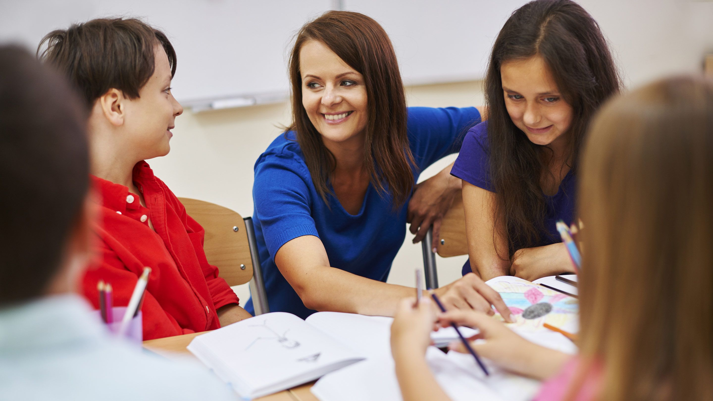 A teacher smiles while talking with students.