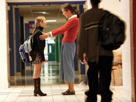 Adult happily greeting a student in the hallway as students move to class