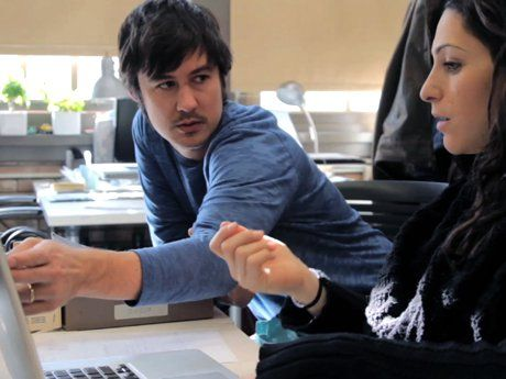 Man showing something on a laptop to a woman
