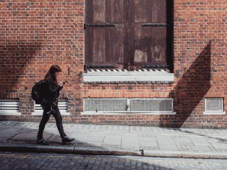 A young woman is walking on the sidewalk past a brick building with her backpack on, looking at her cellphone.