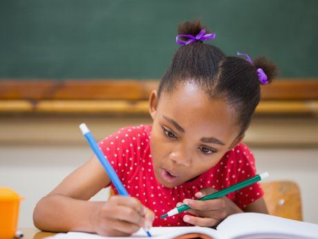 Young girl concentrating on writing with pencils in each hand