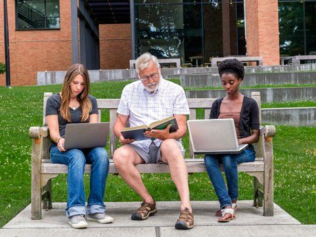 Three adults sitting side-by-side on a bench working on their laptops