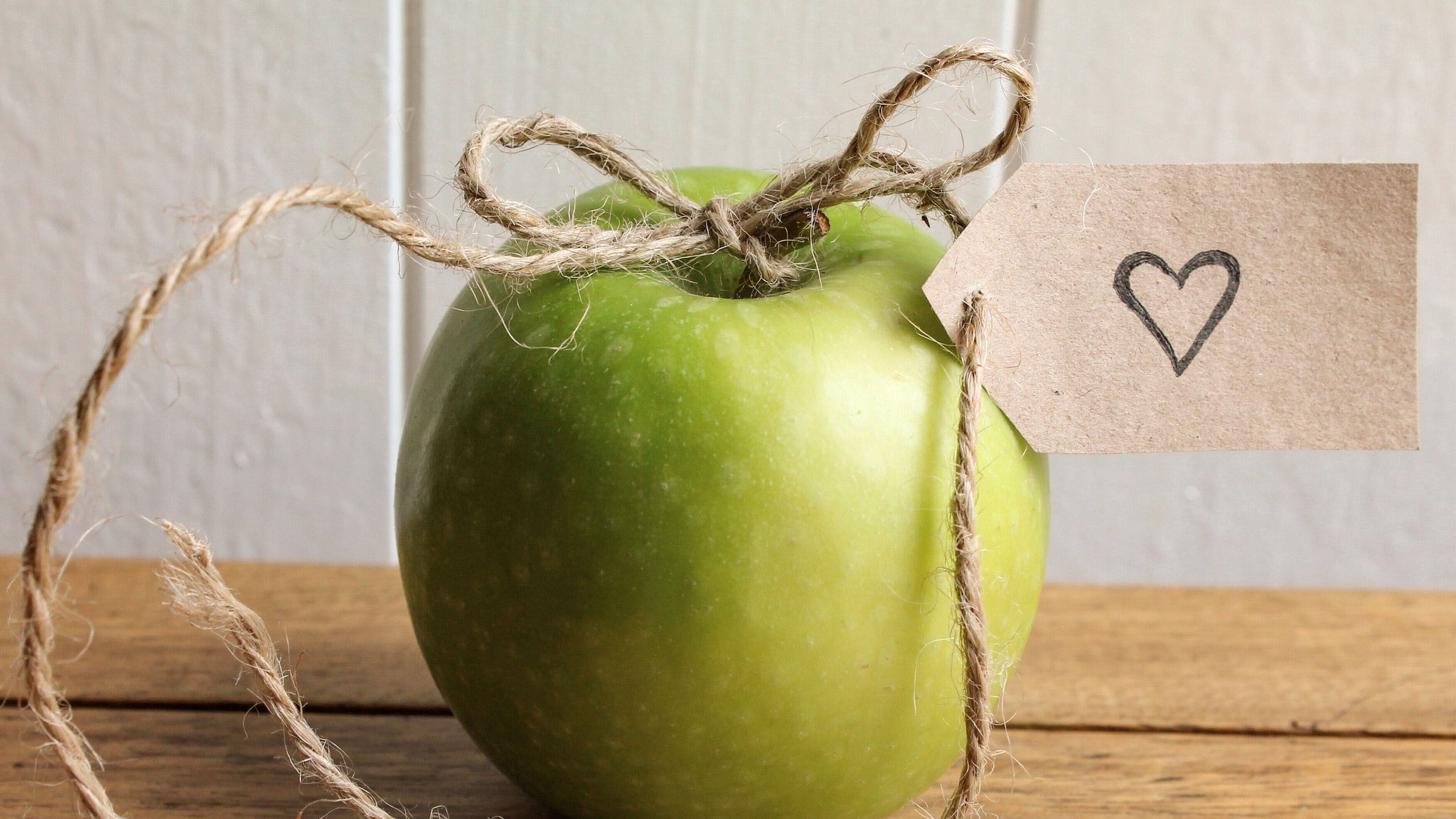 Photo of an apple with a bow on it.