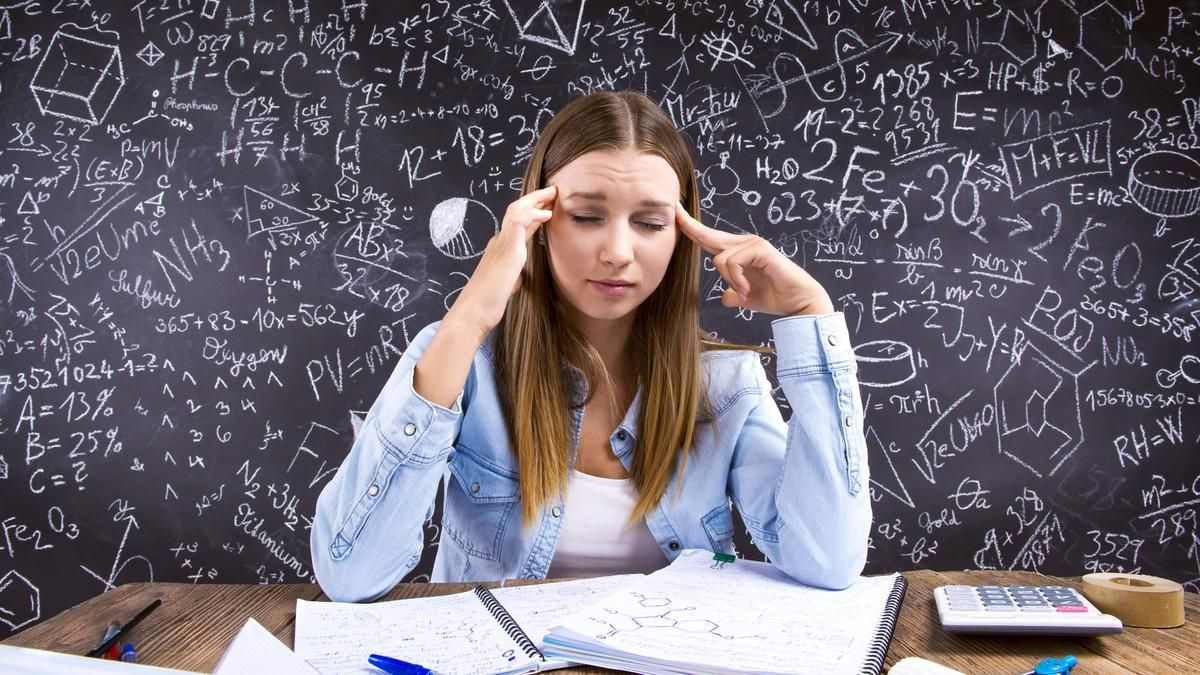 A stressed-out young woman sits in front of a blackboard crowded with numbers and equations.