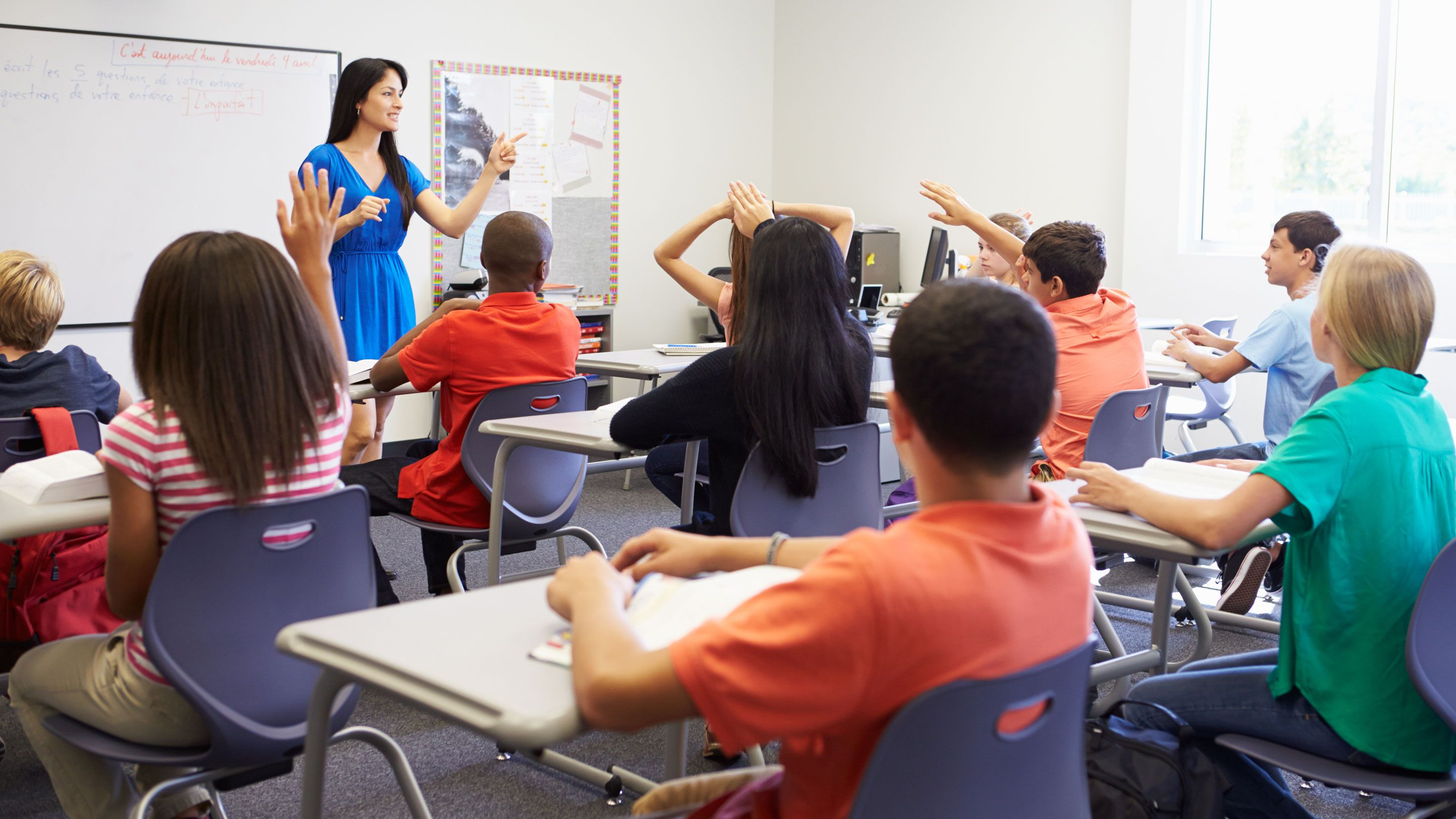 Students raise their hands in a class.