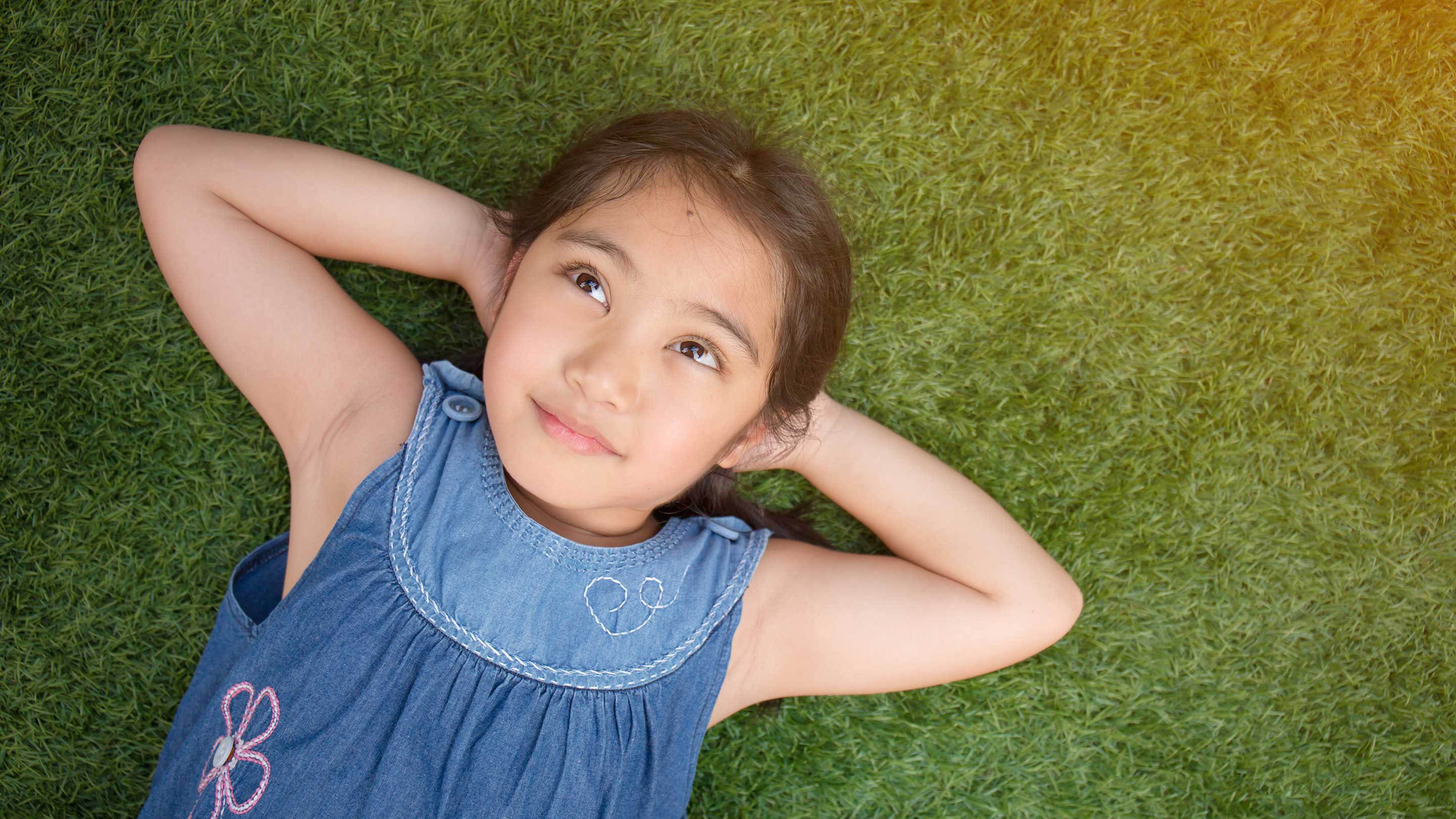 A young girl lies on her back, relaxing on the grass.