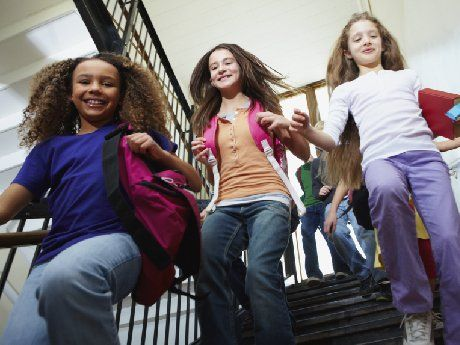 Three young students walking down school stairs