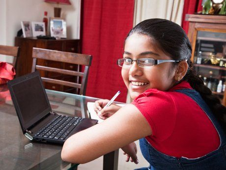 Girl working on her laptop at home on the dining room table