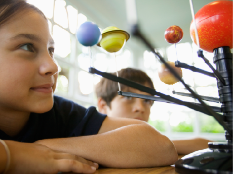 A photo of an elementary-school girl looking at a model of the solar system.