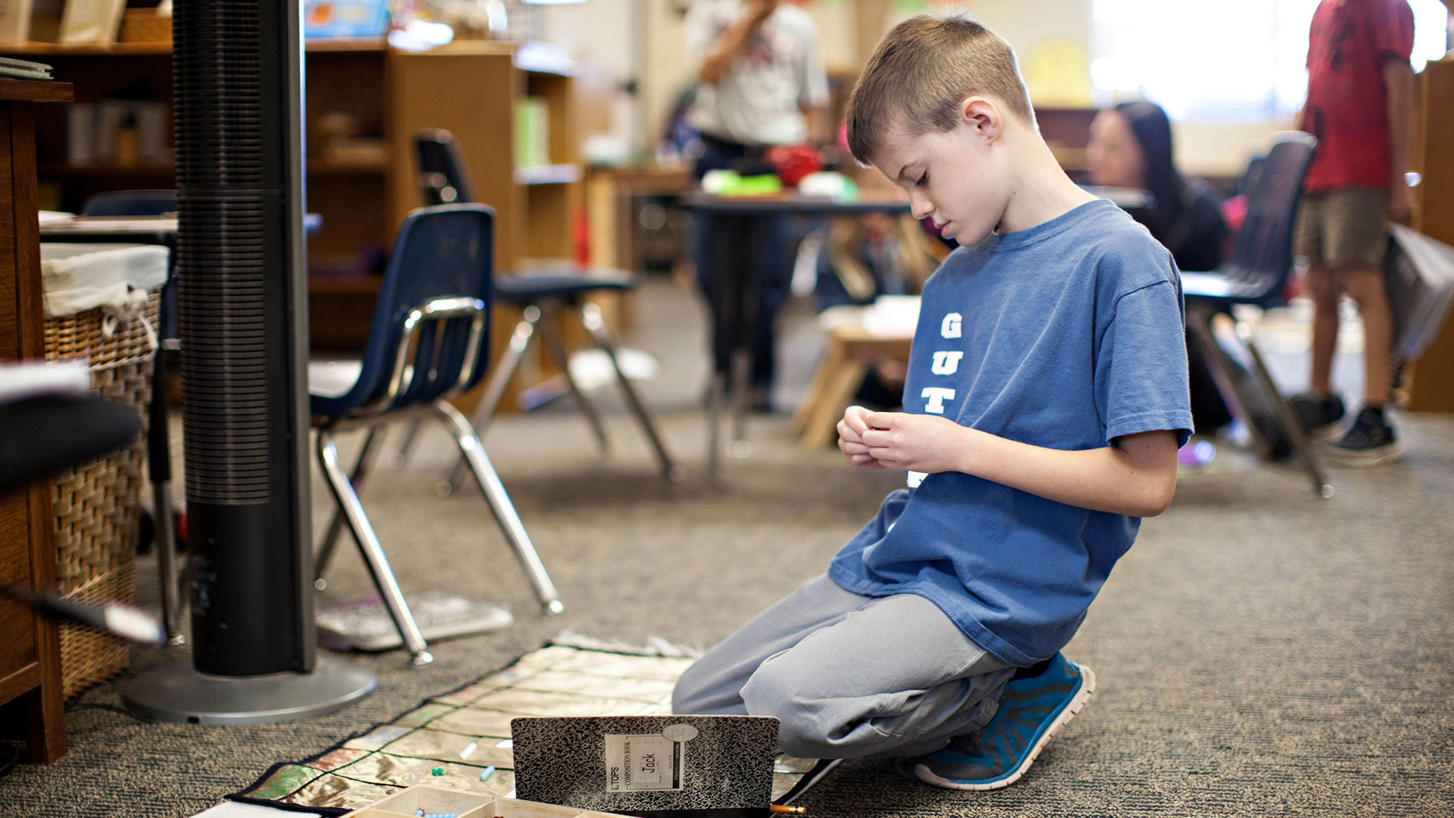 A boy works on the floor in his class.