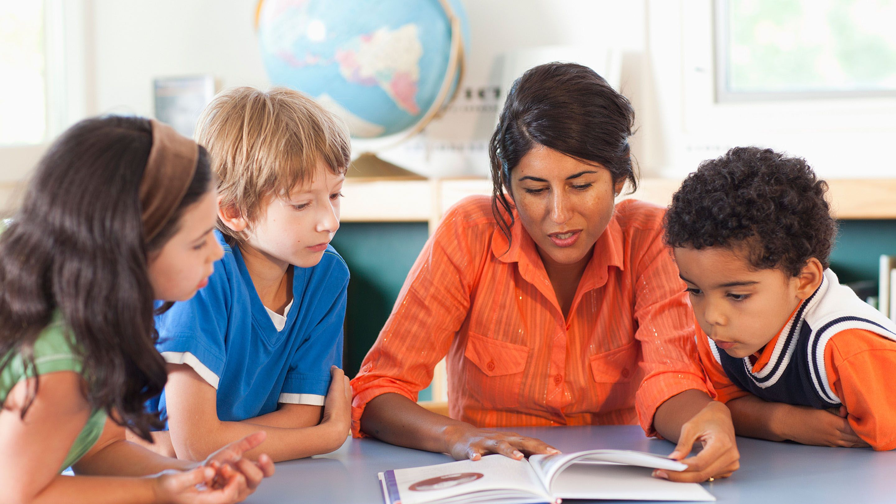 A teacher works with a group of students.