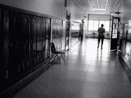 B&W of teacher walking down empty school hallway
