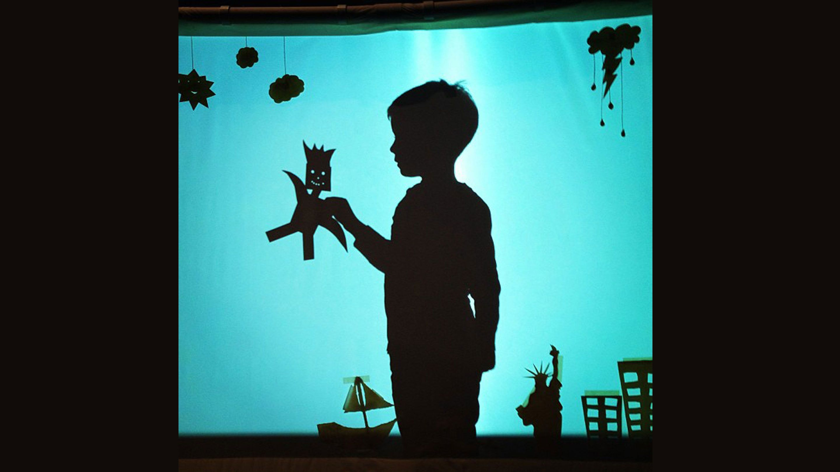 Silhouette of a boy holding a paper puppet