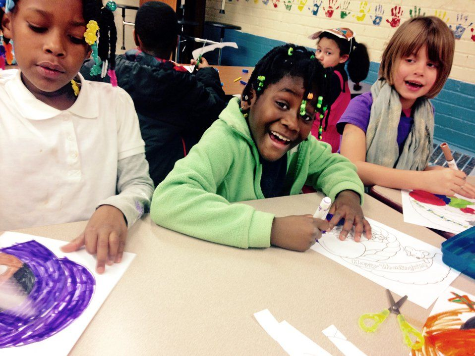 Three elementary school children sitting together at a table in class coloring with markers
