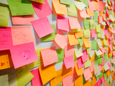 A photo of post-it notes in various bright colors stuck on a wall.
