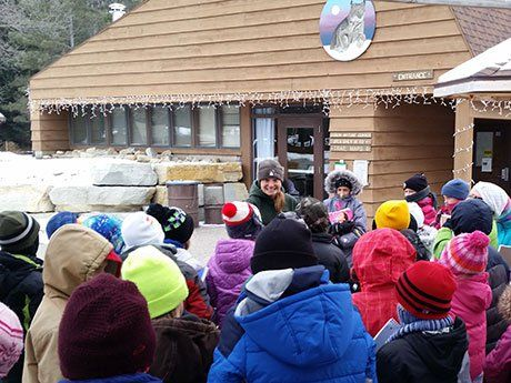 A photo of elementary school children listening to a naturalist at the zoo.
