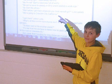 Boy standing in front of class pointing at screen