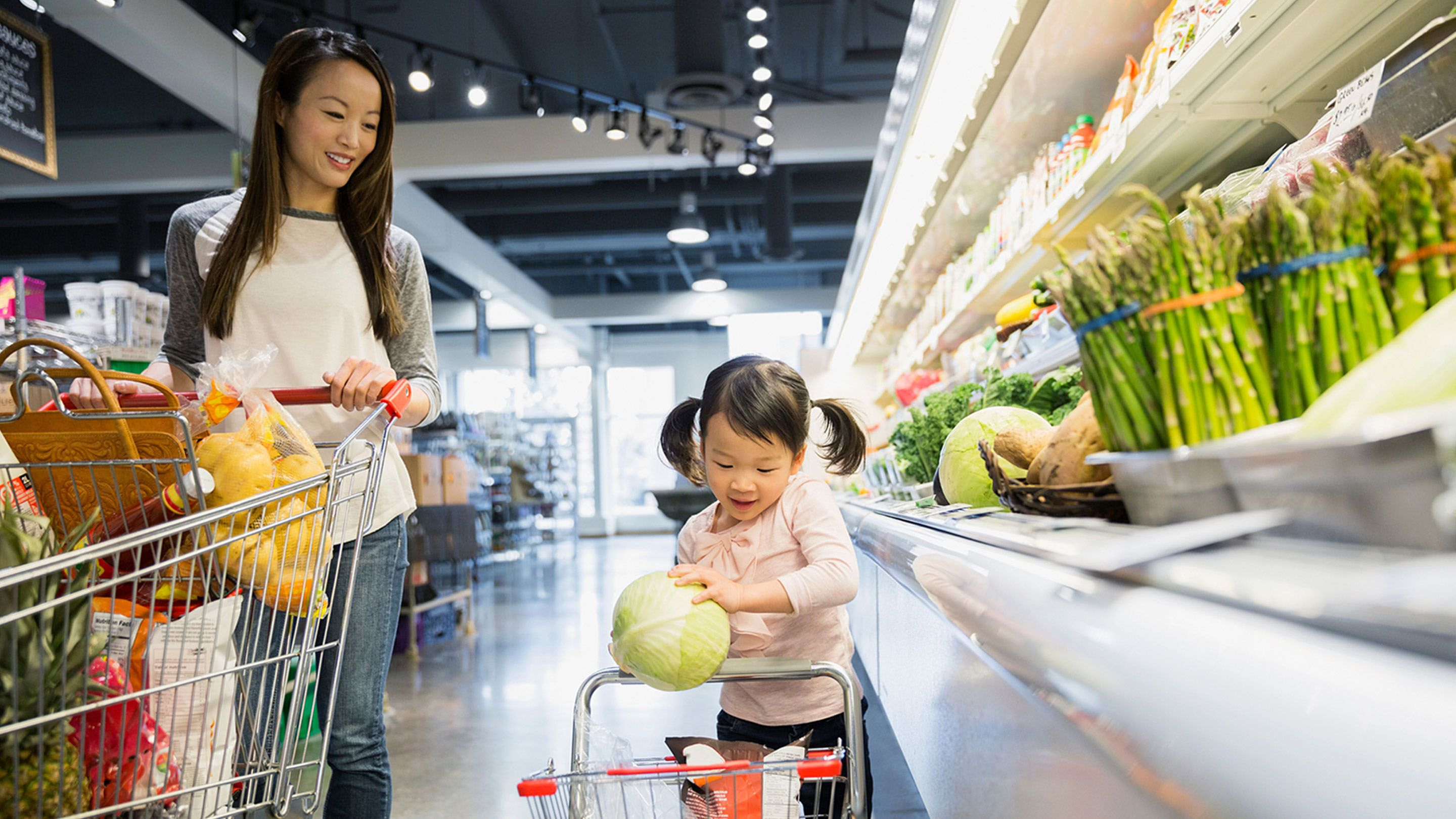 A mom and daughter are walking side by side in the produce aisle of a grocery store, pushing a regular and kid-sized shopping cart.