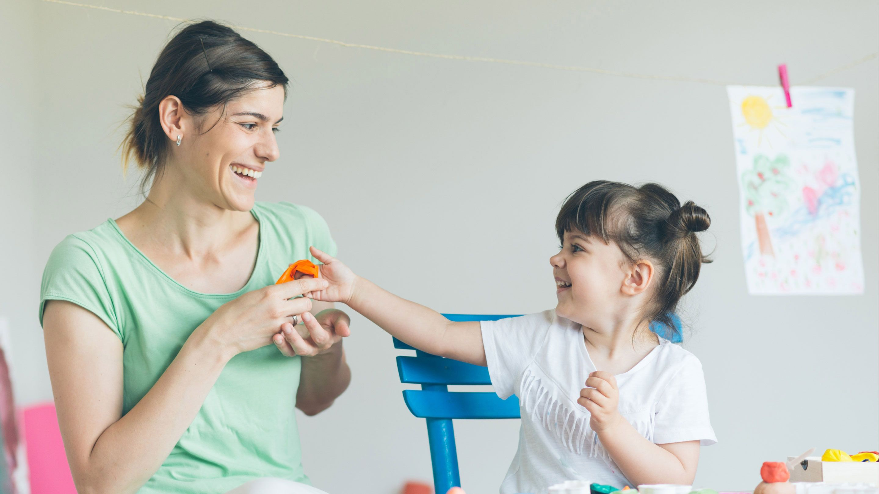 A woman and a young child play together.